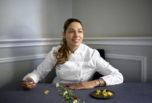 Sabor caribeño. La cocinera, 38 años, sentada en una de las mesas de El Club Allard, con flores de begoña y de pepino y brotes de tatsoi.