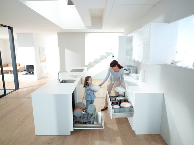 La madre tiene al alcance tres elementos: la niña, los platos y el almacén extraíble. No es la mejor postura para ella pero, por ahora, no tiene solución.