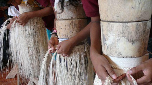 Alumnos tejiendo sombreros finos de paja toquilla.